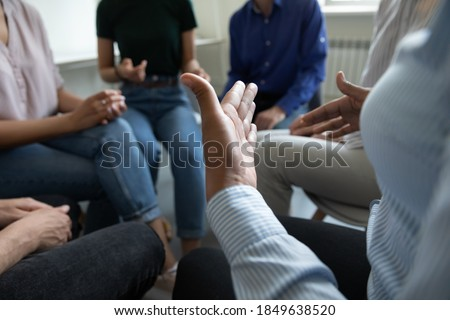Sharing ideas. Close up view of diverse people group gathered in circle at workplace office cabinet to discuss work or self problems, share points of view, listen to mates, feel psychological support Foto stock ©