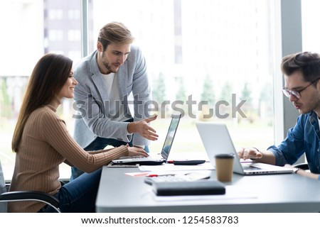 Sharing opinions. Group of young modern people in smart casual wear discussing business while working in the creative office