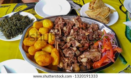 Sharing platter of a traditional Kenyan dish, Nyama Choma accompanied by kachumbari salad, sukuma wiki, chapati and roast potatoes. The roasted goat has been slow cooked outdoors. Eldoret, Africa.