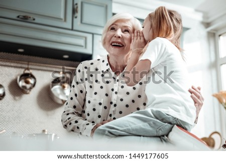 Sharing secrets. Cheerful emotional senior woman smiling and feeling pleased while cute little granddaughter sharing secrets with her