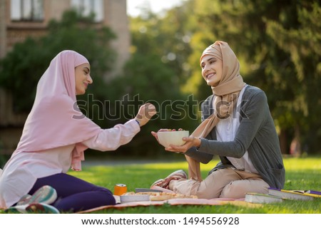 Sharing some blueberries. Friend wearing hijab sharing some blueberries with friend while having lunch outside