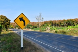 Sharp curve warning roadsign with blue sky background