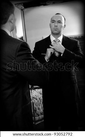 Sharp dressed businessman adjusting his tie (old fashion B&W film grain effect)