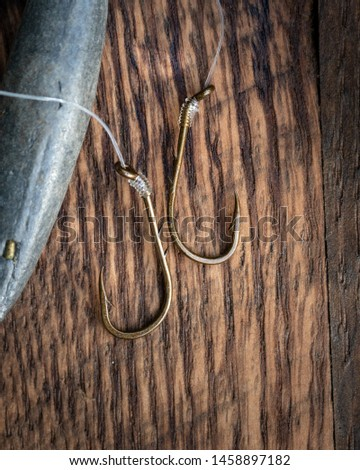 sharp fishing hooks with lead sinker on wooden background #1458897182