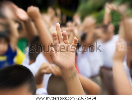 sharp hand raised in blurry schoolyard background zooming in