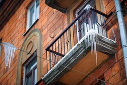 Sharp icicles hanging down on balcony and building facade of old residential building. Sharp icicles on facade of building, dangerous icicles over the road where pedestrians walk, risk of  injury