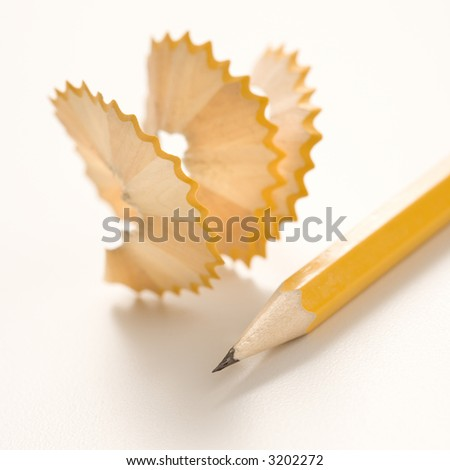 Sharp pencil next to spiral pencil shavings.