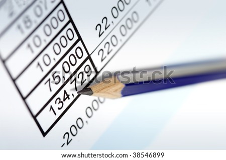 Sharp pencil resting on page of financial figures.  Angled view, soft focus.