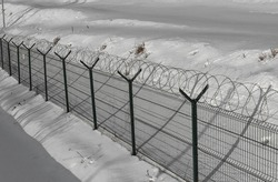 Sharp razor wire on mesh fence. Basic fences for objects of the penitentiary system, border control, prison, restricted area. Winter time scene