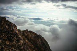 Sharp rocks on background of mountain peak above cloudy sky. Mountain vertex floats in thick clouds. Minimalist landscape with mountain top above dense low clouds. Scenic minimalism over dense clouds.