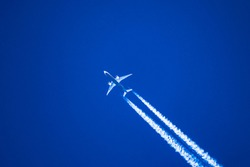 Sharp telephoto close-up of jet plane aircraft with contrails cruising from Taipei to Chicago, altitude AGL 37,000 feet, ground speed 547 knots.