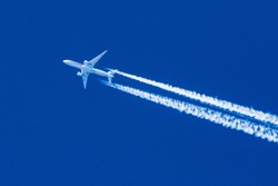 Sharp telephoto close-up of jet plane aircraft with contrails cruising from Tokyo to Chicago, altitude AGL 35,000 feet, ground speed 472 knots.