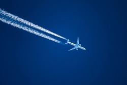 Sharp telephoto close-up of jet plane aircraft with contrails cruising from Tokyo to Chicago, altitude AGL 35,000 feet, ground speed 533 knots.