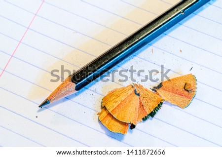 Sharpened pencil and shavings on a blank  notebook lined page #1411872656