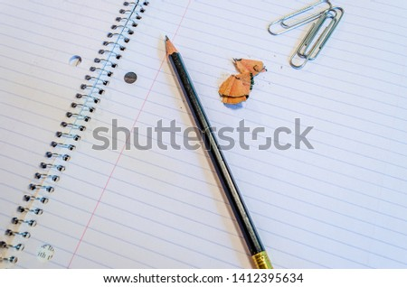 Sharpened pencil, shavings and paperclips on a blank wire-bound notebook lined page #1412395634