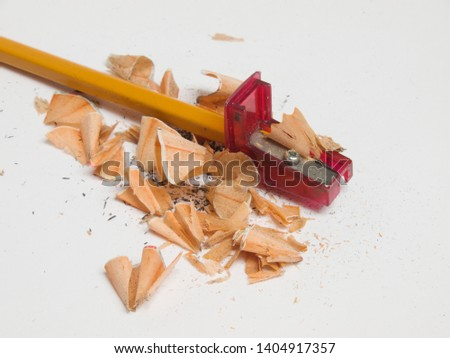 Sharpened pencil with the sharpener and cutted wood residues and graphite, on the white background