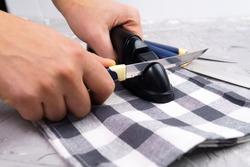 Sharpening a knife. Close-up of a man using a sharpener to sharpen a knife blade