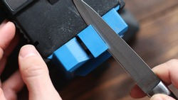 Sharpening a knife on an electric sharpener at home. The man's hand drives the knife blade between the blue sharpeners, dust flies on the machine.