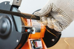 Sharpening the blade of a lawn mower with an electric sharpener. Hands in work gloves hold and sharpen the blade