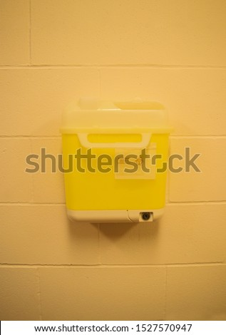 Sharps container for used needles, attached to wall, ideal for health and wellness industry with room for content, ideal for news, print or web.