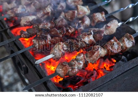 Shashlik preparing on a barbecue grill over charcoal. Pieces of meat on skewers. Shish kebab prepare on fire. #1112082107