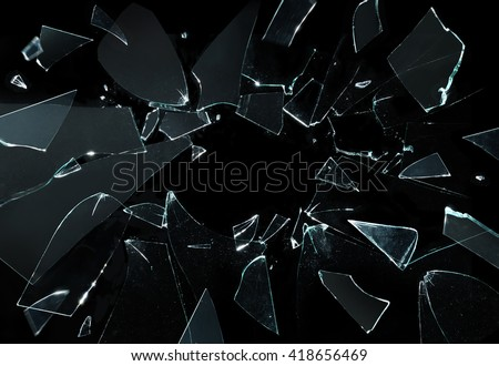 Shattered and broken glass pieces isolated on black