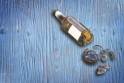 Shattered beer bottle resting on the ground - alcoholism concept with copy space against a wooden background