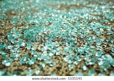 Shattered glass from a car window lays scattered on the sidewalk.