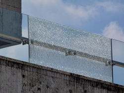 Shattered glass railing or balustrade & stone panel under blue sky with white clouds. broken laminated tempered safety glass. construction and building industry concept. stainless steel glass brackets