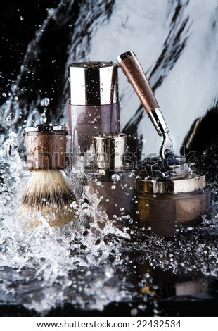 Shaving accessories and water. Close up of male shaving accessories with water background and splashes.