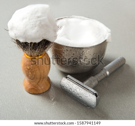 Shaving blade, shaving brush and bowl with shaving foam. In drops of water. Still life.