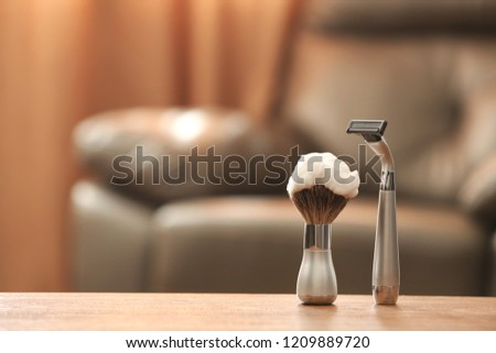 Shaving brush and razor on table against blurred background with space for text