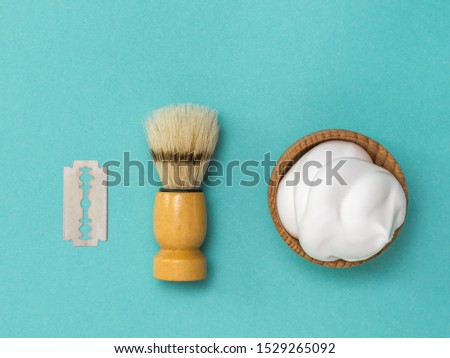 Shaving brush and shaving foam in a wooden bowl. Set for care of a man's face. Flat lay.
