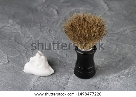 shaving brush and shaving foam on a concrete background