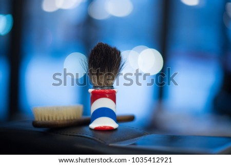 Shaving brush shaving beard on a blue blurred background, beauty parlor, barbershop. #1035412921