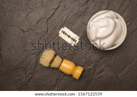 Shaving brush, shaving foam, and a blade on a stone table. Set for care of a man's face. Flat lay.