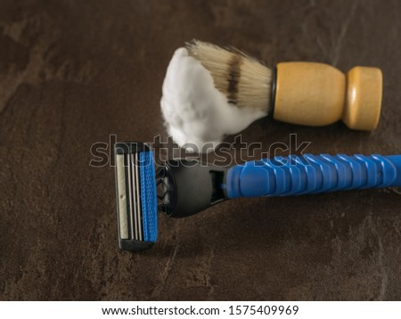 Shaving brush with shaving foam and razor blue on a stone background. Set for care of a man's face. Flat lay.