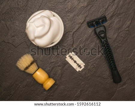 Shaving foam, shaving machine and shaving brush with wooden handle on a dark stone background. Set for care of a man's face. Flat lay.