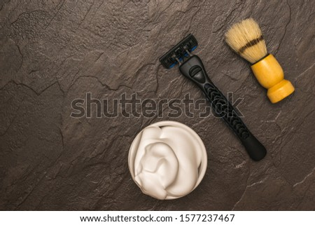 Shaving foam, shaving machine and shaving brush with wooden handle on stone background. Set for care of a man's face. Flat lay.