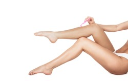 Shaving legs. Spa, depilation and bodycare concept. Legs of healthy girl shaving it carefully. Isolated on white background. Woman removing hair on legs with razor. Woman shaving legs in bathroom.