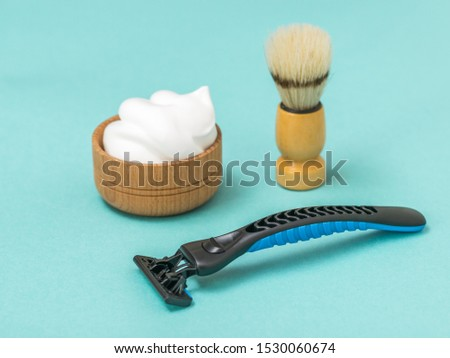 Shaving machine with shaving foam and brush on a blue background. Set for care of a man's face.