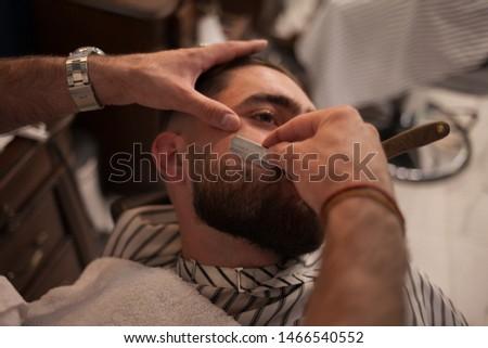 Shaving procedure of beards in barbershop. Barber shaves beard of the client