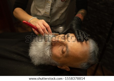 Shaving process of beards in Barbershop. Master makes a haircut beard client with vintage straight razor.