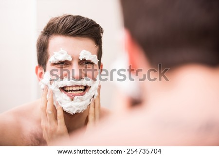 Shaving with fun. Rear view of playful young man with shaving cream on his face is standing in front of the mirror and smiling.