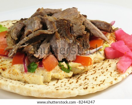 Shawarma style beef on a pita, with hummus, lettuce, tomato, red onions, and a side of turnips pickled in beet roots.