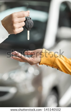 She has made a right choise. Close-up shoot of the car salesman hand giving the key to female owner