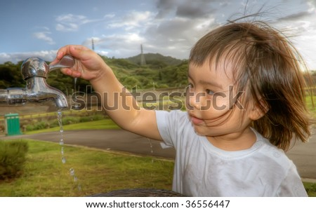 She is a happy baby washing her hand in the outdoor.