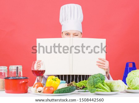 She is a super cook. Lady cook looking for cooking recipe in cookbook. Pretty woman reading cook book in kitchen. Cute cook housekeeper at kitchen table, copy space.