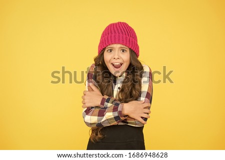 She is cold. Unhappy little child feel cold yellow background. Small girl shiver in cold weather headwear. Crispy autumn or winter season. Chilly and cold. Coldness.