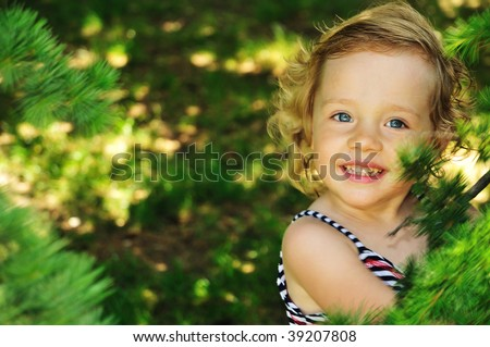 she is cute, smiling blond girl, she is happy to be in forest